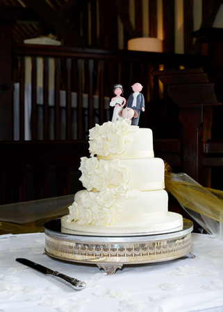 tier: Wedding cake is three tier with topper showing couple and dog Stock Photo