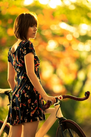 woman with bicycle in the garden  photo