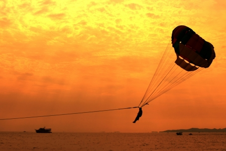 parasailing: A silhouette of a parasailing on Pattaya beach  Stock Photo