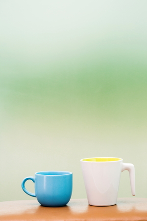 Two cups on the table blur background. Imagens