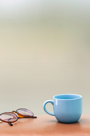 blue cup and eyeglass on the table blur background.