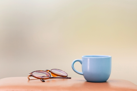 blue cup and eyeglass on the table blur background