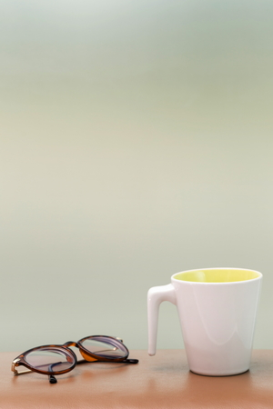 Cup and eyeglass on the table blur background