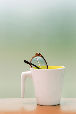 eyeglass in cup on the table blur background.