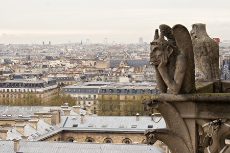 grotesque: Notre Dame de Paris: Chimera overlooking the skyline of Paris at a cloudy day Editorial