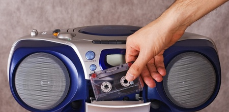 inserting: Inserting a cassette into tape recorder Stock Photo