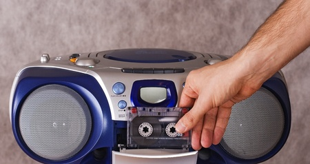 Inserting a cassette into tape recorder Stock Photo