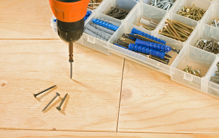 cordless: cordless drill, screws and toolbox on a wood background