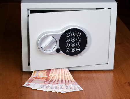 roubles: Safe with roubles on wooden shelf Stock Photo