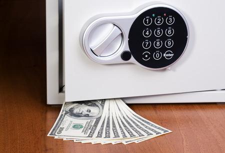 caja fuerte: Caja de seguridad con los dólares en el estante de madera Foto de archivo