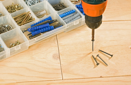 cordless drill, screws and toolbox on a wood background