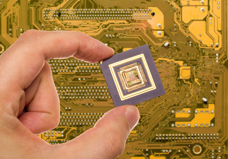 printed: Microprocessor in hand over printed circuit board Stock Photo