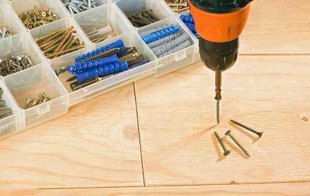 toolbox: cordless drill, screws and toolbox on a wood background