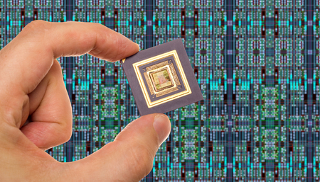 microprocessors: Microprocessor in hand in front of chip layout