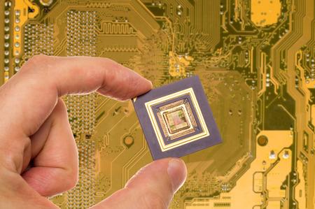 microprocessor: Microprocessor in hand over printed circuit board Stock Photo
