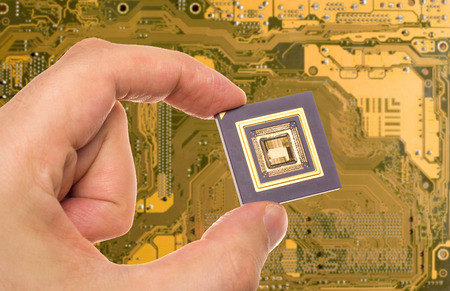 Microprocessor in hand over printed circuit board Stock Photo