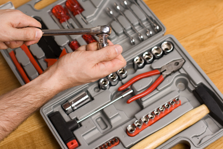 ratchet: Hands holding ratchet and head over toolbox with different instruments