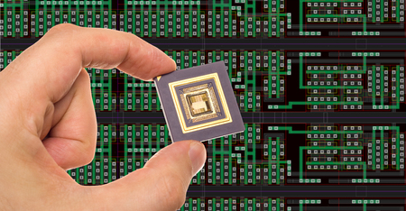 Ic: Microprocessor in hand in front of chip layout