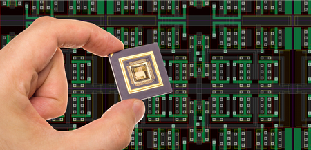 microprocessor: Microprocessor in hand in front of chip layout