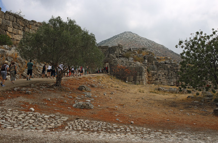 Mycenae, Greece, September, 7, 2016. Tourists walk through the Lions Gate of Mycenae citadel. It was built more than 3000 years ago.
