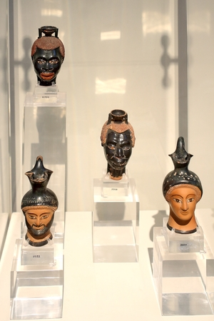 Athens, Greece, September, 03, 2016. Greek exhibits in museum of archaeology, Athens, Greece. Small vessels for perfume have a shape of humans head.