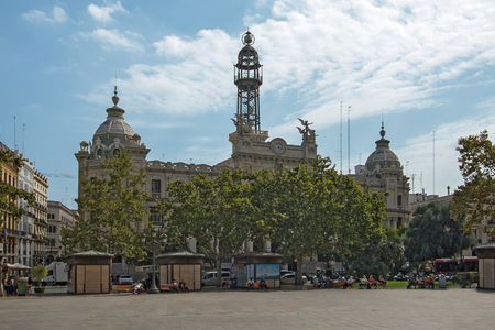Valencia, Spain - September, 12, 2018. People rest at the square near Valencia Post Office. The modern style building is one of the main historical landmarks of the city due to its steel tower Editorial
