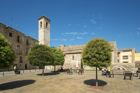 Montblanc, Spain - September, 09, 2018. People rest near the church of Sant Miquel in Montblanc town. The church was built in 13th century. Editorial