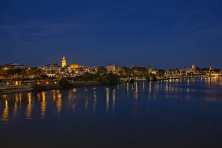 View of Seville historic center from the Bridge of Isabella II at night Archivio Fotografico