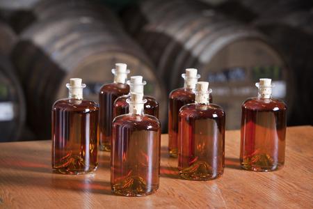 botella de whisky: Sólo embotellada licor con barriles en el fondo Foto de archivo