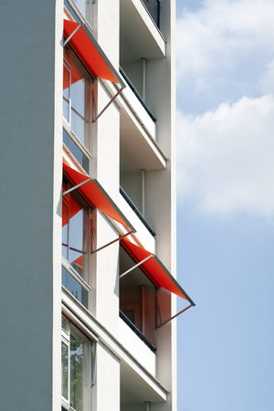 awnings: Orange awnings on a white apartment block Stock Photo