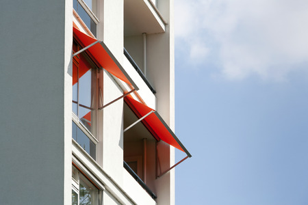 Orange awnings on a white apartment block Stockfoto