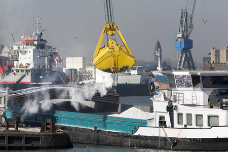foreign trade: Big grab bulk loading into a barge in the Port of Rotterdam Stock Photo