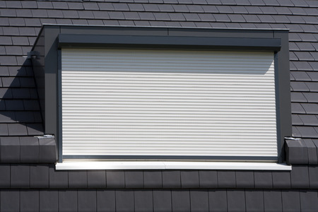 security shutters: Porthole with a white rolling shutter on a black roof Stock Photo