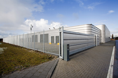 metal gate: Well secured metal industrial building Stock Photo