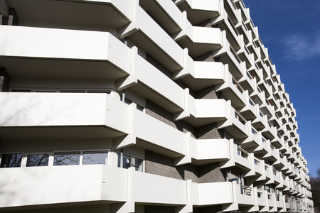 apartment block: Apartment block from the 70's in a green environment. At the moment a lot of the apartments are used as social housing and for the elderly.  The flats are located in a tranquil area with a lot of grass, water, bridges and pavement. The white concrete ba