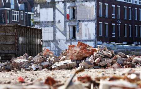 deconstruction: Demolition of residential district Crooswijk in Rotterdam, the Netherlands. Theres some of rubble around a builders skip. Stock Photo