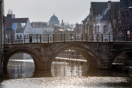 A backlight photo of a bridge (Hoogbrug) in the center of Mechelen in Belgium. A couple is walking on the bridge. Under the bridge two persons are walking on the floating wooden walkway. On the walkway you can make a river walk of several kilometers. Ther