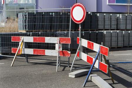 materiales de construccion: Camino cerrado signo y una barrera roja y blanca rayada la construcci�n debido a la construcci�n de carreteras. Los materiales de construcci�n, ladrillos y azulejos son en el fondo. Foto de archivo