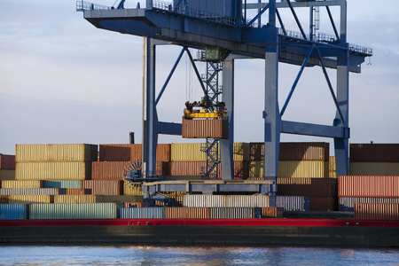 Gantry crane lifting a container from stack to a barge