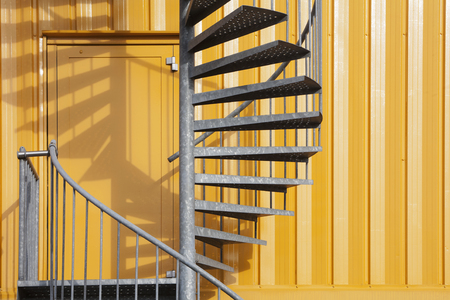 steps and staircases: Yellow building with spiral metal staircase