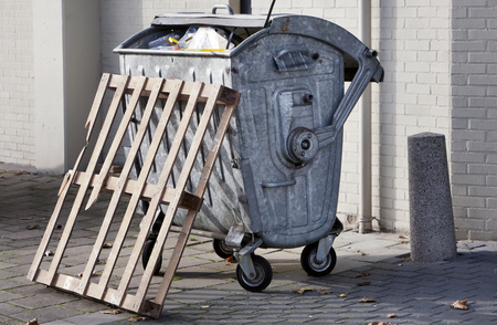 Metal wheeled garbage container and a broken pallet