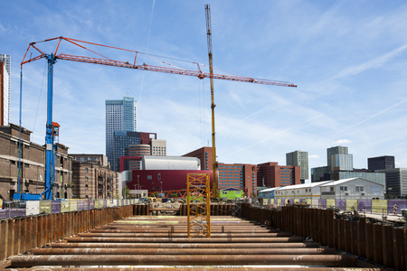Construction site with 2 cranes in Rotterdam, in the Netherlands. Modern architecture and old warehouses in the background. Stock Photo
