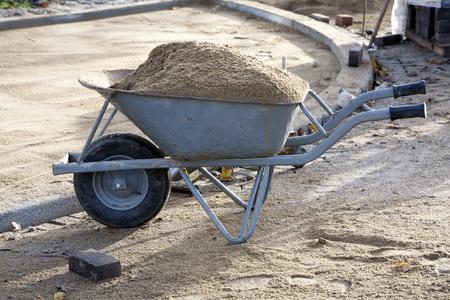 loaded: Wheelbarrow of pavers loaded with sand Stock Photo