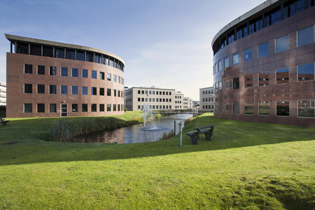Office park met gras, water, fontein, brug en bankjes