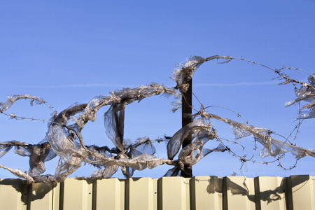 plastic waste: Plastic waste caught by barbed wire
