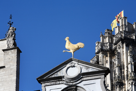 irritating: Facade of buildings in Mechelen in Belgium. A golden rooster is irritating a lion neighbor. In the background Flemish flags on the Rumbold tower of the cathedral Rumbold Stock Photo