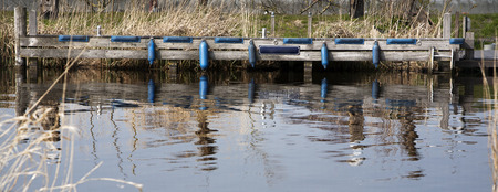 mooring bollards: Tranquil scene of a jetty with blue boat fenders.  In the middle of the jetty is a blue blank sign that can be filled in. Reflections in the water of some mooring bollards.