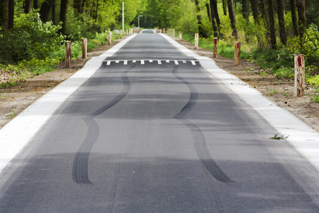 skid: Skid marks in front of speed bump on a asphalt country road Stock Photo