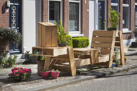 sociable: Wooden benches and flowers in front of the door on this street in the residential district Kralingen in Rotterdam, the Netherlands.