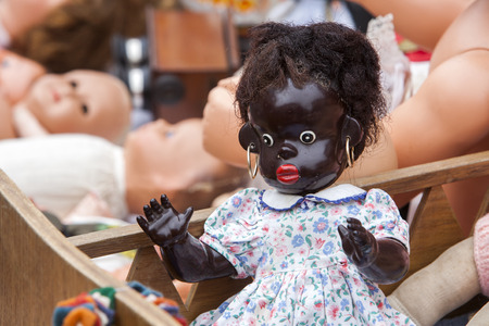 jumble: Second hand dolls at a jumble sale in France. Black doll with golden earrings in a wooden crib on the foreground and some white dolls in the background.